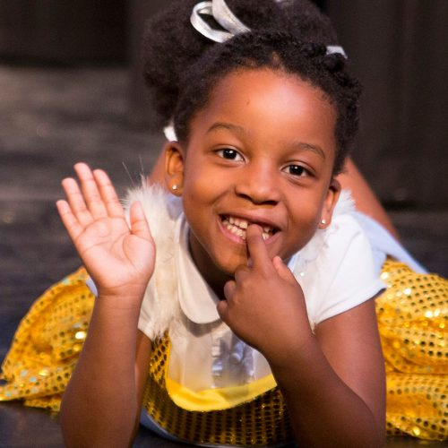 Young actress waving on stage in Hairspray the musical.